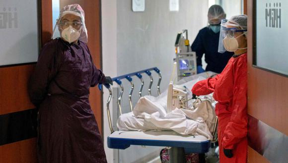 Trabajadores de la salud que transportan a un paciente de COVID-19 esperan en la entrada de la Unidad de Cuidados Intensivos (UCI) del Hospital General, en Medellín, Colombia. (AFP/JOAQUIN SARMIENTO).