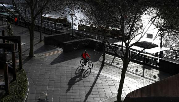 Esta imagen tomada el 16 de julio de 2021 muestra a un ciclista solitario que recorre Southbank en Melbourne (estado de Victoria) luego de un nuevo bloqueo en medio de un resurgimiento de casos de coronavirus. (ASANKA BRENDON RATNAYAKE / AFP).