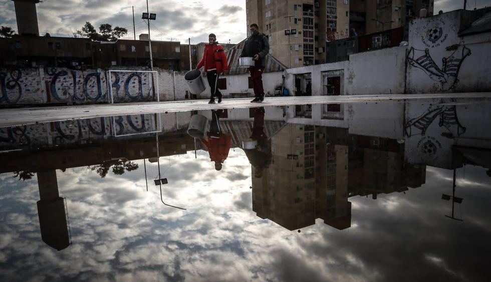 Dos personas caminan con ollas para una comida popular en el barrio Fuerte Apache, provincia de Buenos Aires (Argentina). (EFE/Juan Ignacio Roncoroni).