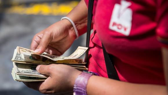 Un bombero cuenta dólares en una estación de gasolina en Caracas (Venezuela). (Foto referencial: EFE/Miguel Gutiérrez)