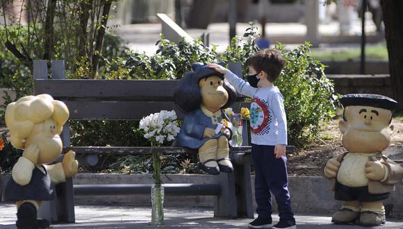 Un niño toca una estatua que representa a Mafalda, un personaje de tira cómica creado por el dibujante argentino Joaquín Salvador Lavado, conocido como Quino, flanqueada de flores en Mendoza, Argentina, el 30 de septiembre de 2020, el día de su muerte. Quino falleció el miércoles a los 88 años, confirmó su editor. (Foto: Andrés LARROVERE / AFP)