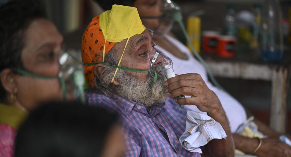 Pacientes de coronavirus respiran con la ayuda del oxígeno proporcionado por un Gurdwara, un lugar de culto para los sijs, en una carpa instalada a lo largo de la carretera de Ghaziabad, en la India. (Foto de Sajjad HUSSAIN / AFP).