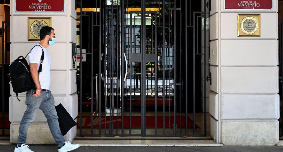 """En Roma, cientos de carteles de protesta cuelgan de puertas y vitrinas: """"Sin la ayuda del gobierno, NO podemos abrir"""".  Imagen de un hombre caminando por la parte de afuera de un hotel en la zona de Via Veneto en la capital de Italia. (Tiziana FABI / AFP)."""