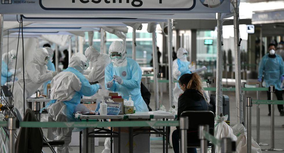 Personal médico toma muestras para diagnosticar coronavirus de un pasajero extranjero en una cabina de pruebas fuera de un aeropuerto internacional. (Foto: AFP/Jung Yeon-je)