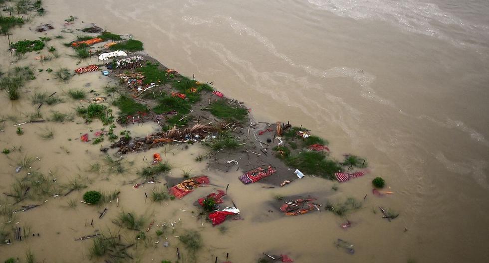 El aumento del nivel del agua del río Ganges lava la escasa capa de suelo que revela las tumbas poco profundas de presuntas muertes por coronavirus en India, el 27 de junio de 2021. (SANJAY KANOJIA / AFP).