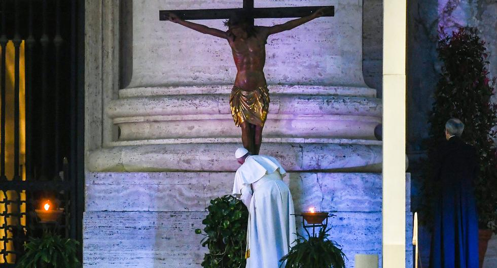Pope Francis kisses a miraculous crucifix that in 1552 was carried in a procession around Rome to stop the great plague, that was brought from the San Marcello al Corso church in Rome, during a moment of prayer on the sagrato of St Peter�s Basilica, the platform at the top of the steps immediately in front of the fa�ade of the Church, to be concluded with the Pope giving the Urbi et Orbi Blessing, on March 27, 2020 at the Vatican. (Photo by Vincenzo PINTO / AFP)