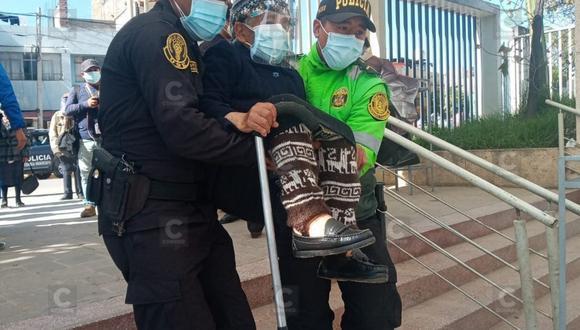 La edad avanzada de Juana no le permitió caminar con rapidez por lo que los efectivos de la Policía Nacional optaron por cargarla para que pueda ingresar al local de vacunación a la espera de su turno.