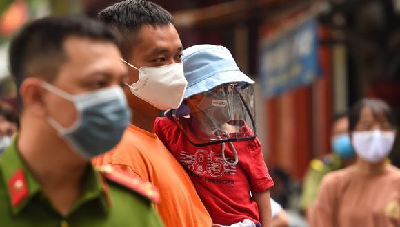 Un grupo de residentes esperan ser examinados en un improvisado centro de pruebas rápidas en Hanoi, mientras Vietnam registra un aumento en los casos del coronavirus. (NGUYEN / AFP)
