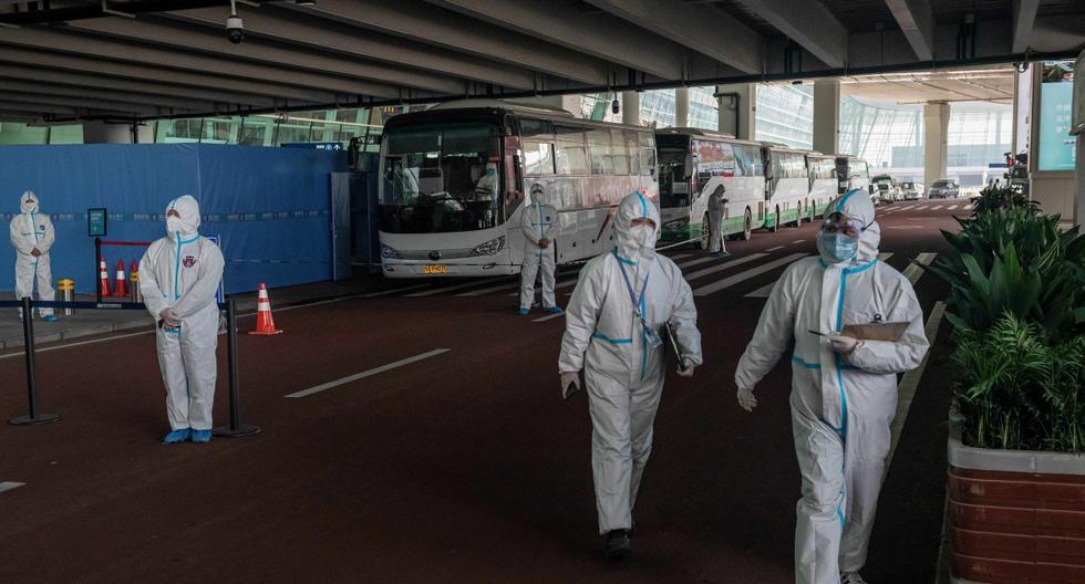 Los trabajadores de la salud con trajes de protección personal caminan junto a los autobuses en una sección acordonada en el área de llegadas internacionales del aeropuerto internacional de Wuhan el 14 de enero de 2021. (Foto de NICOLAS ASFOURI / AFP).