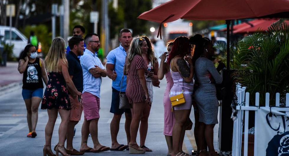 People stand in queue to enter a restaurant on Ocean Drive in Miami Beach, Florida on June 26, 2020.  They are itching for a good time after months of lockdown, and may the coronavirus be damned: young adults in Florida are fueling a dangerous rise in COVID-19 infections. Feeling immortal, these fun-crazed people are finding ways to gather and party even though many bars and nightclubs remain closed as the Sunshine State reopened its economy this month. / AFP / CHANDAN KHANNA