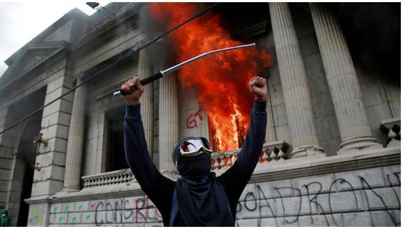 Un hombre protesta en frente del Congreso de Guatemala en llamas, ocasionado por manifestantes que protestan contra el gobierno del presidente Alejandro Giammattei. (Foto: EFE/Esteban Biba)