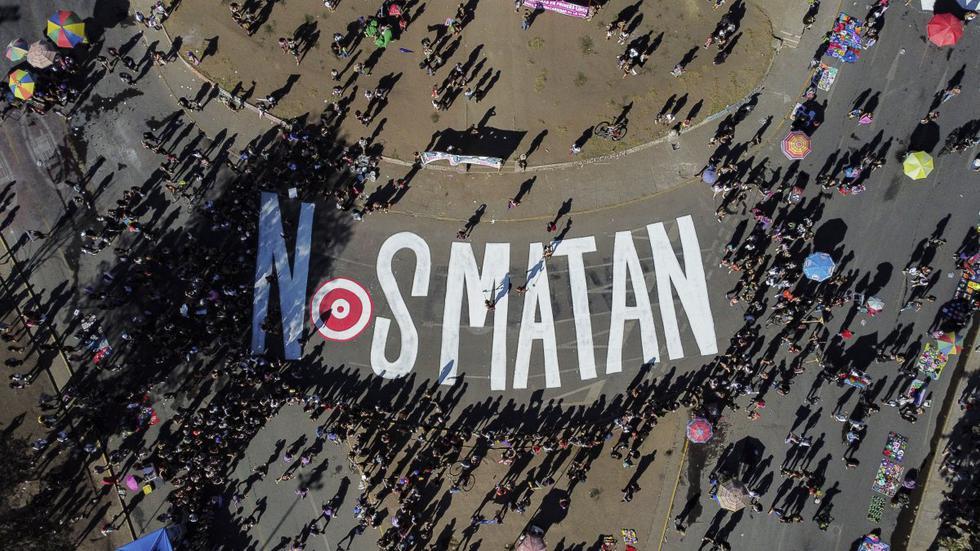 """Una señal que dice """"Nos están matando"""" se ve en la calle mientras las mujeres chilenas participan en una manifestación para conmemorar el Día Internacional de la Mujer en Santiago, el 8 de marzo de 2021. (Foto: MARTIN BERNETTI / AFP)"""