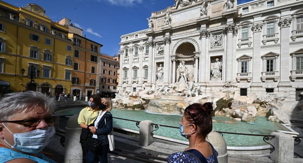 Imagen referencial. Ciudadanos que usan mascarillas para protegerse del coronavirus posan junto a la Fontana di Trevi en el centro de Roma, Italia, el 25 de setiembre de 2020. (Foto de Vincenzo PINTO / AFP).