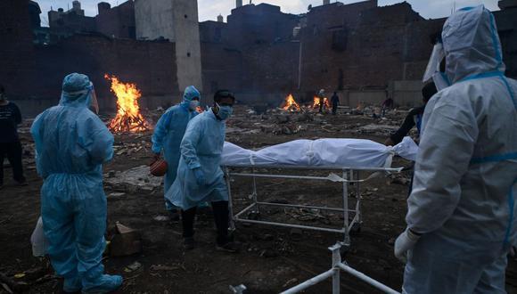 Familiares con trajes de equipo de protección personal (EPP) llevan el cuerpo de una persona que murió debido al coronavirus Covid-19, en un crematorio en Nueva Delhi el 6 de mayo de 2021. (Foto de Prakash SINGH / AFP).