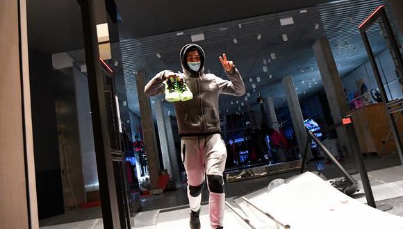 Un hombre muestra el signo de la victoria mientras sale de una tienda con un par de zapatos durante los enfrentamientos tras una manifestación contra el encarcelamiento del rapero español Pablo Hásel, en Barcelona. (Pau BARRENA / AFP)