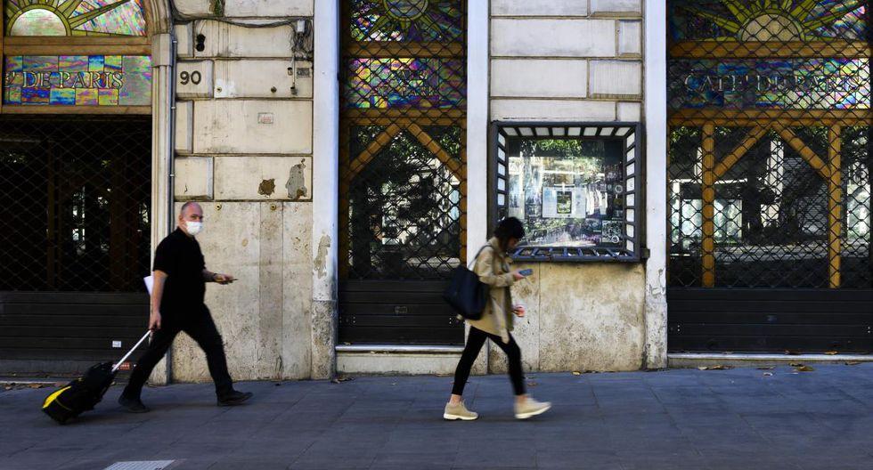 La gente pasa frente a un café cerrado en Via Veneto, en el centro de Roma, mientras el país alivia su bloqueo para frenar la propagación del coronavirus. (Tiziana FABI / AFP).