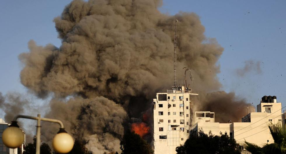 Denso humo y fuego se elevan desde la torre Al-Sharouk mientras se derrumba después de ser golpeada por un ataque aéreo israelí, en la ciudad de Gaza. (Foto de Mohammed ABED / AFP).
