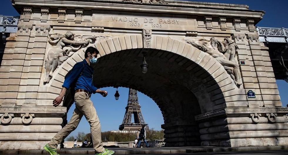 Un peatón que usa mascarilla para protegerse del coronavirus camina por el puente Bir Hakeim, cerca de la Torre Eiffel, en París, Francia. (Foto: EFE / EPA / IAN LANGSDON).