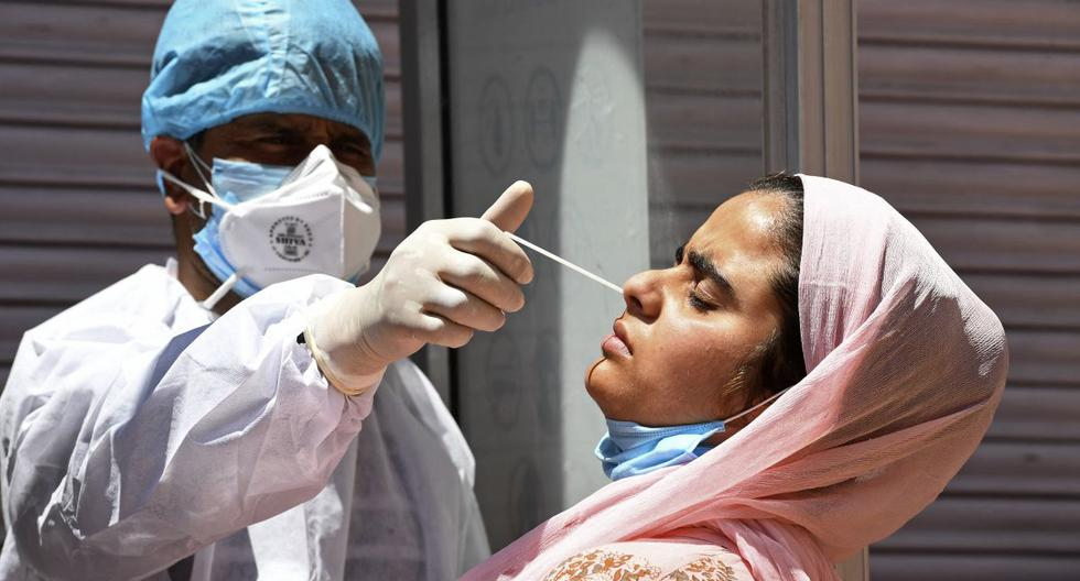 Un trabajador de la salud toma una muestra de hisopo nasal de una mujer para realizar la prueba del coronavirus Covid-19 en un centro de pruebas en Srinagar, India. (Foto de TAUSEEF MUSTAFA / AFP).