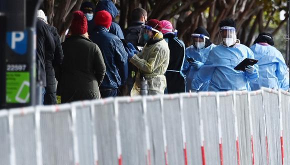 En esta foto de archivo, tomada el 18 de noviembre de 2020, los trabajadores del sitio de pruebas de COVID-19 Judiciary Square obtienen información de personas que esperan en una fila, en Washington DC. (MANDEL NGAN / AFP)
