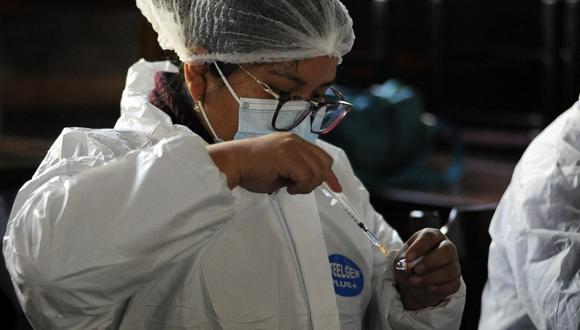Una trabajadora de salud prepara una dosis de la vacuna contra Covid-19, en la Universidad Superior de San Andrés (UMSA), en La Paz. (Foto: Jorge Bernal / AFP)