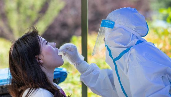 Un trabajador de salud realiza una prueba de coronavirus a una mujer en la Universidad de Wuhan. (Foto: China OUT/AFP).