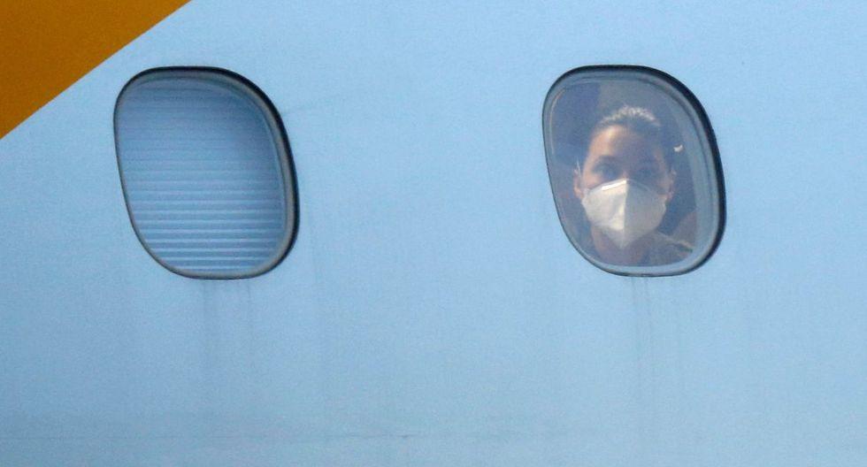 Una pasajera asomándose por la ventana ante su llegaba a Brasil tras pedir ayuda para ser repatriada. (Reuters).