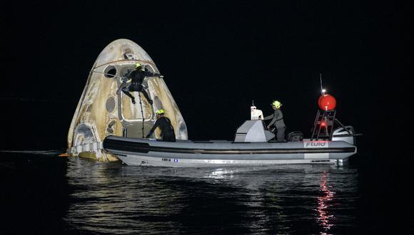Esta imagen, de cortesía de la NASA, muestra a los equipos de apoyo que trabajan en torno a la nave espacial SpaceX Crew Dragon Resilience poco después de que aterrizara con los astronautas Mike Hopkins, Shannon Walker, Victor Glover y Soichi Noguchi. (Bill INGALLS / NASA / AFP)