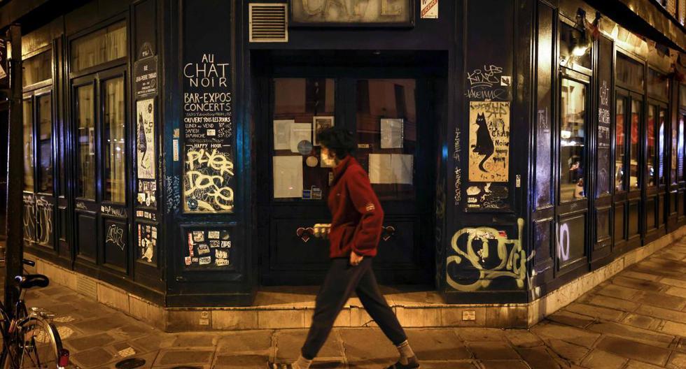 Imagen referencial. Un hombre pasa frente al famoso bar cerrado Au Chat Noir en París (Francia), el 6 de octubre de 2020. (AFP / THOMAS COEX).
