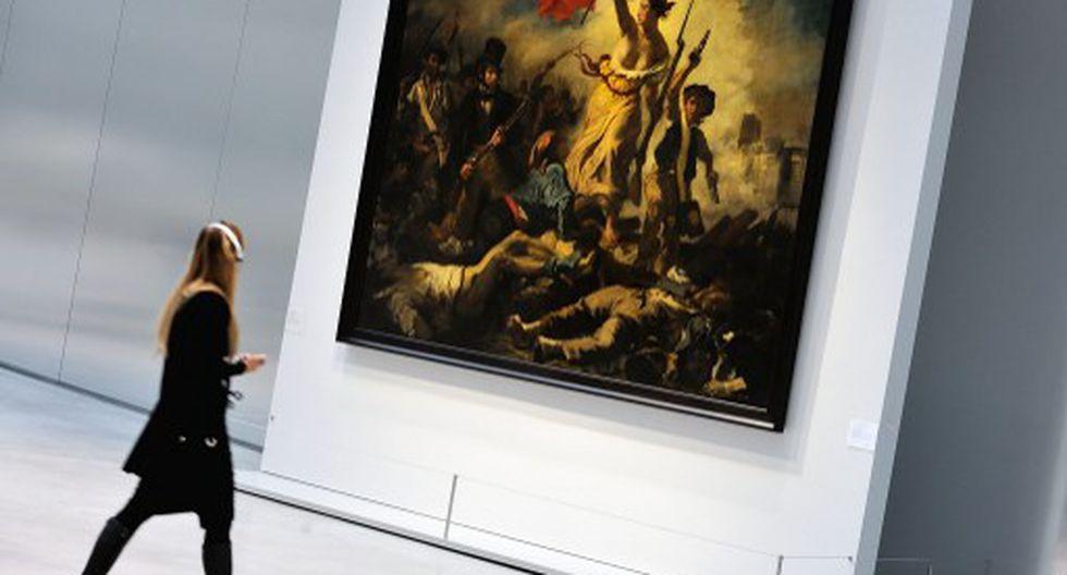 """Mujer pinta con marcador negro el famoso cuadro """"la Libertad guiando al pueblo"""" de Delacroix"""