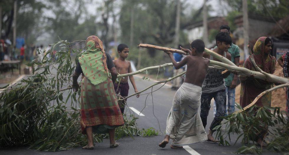 Los lugareños intentan quitar un árbol desarraigado de la carretera principal después de que el ciclón Amphan tocara tierra, en la aldea de Bokkhali cerca de la Bahía de Bengala, India, el 21 de mayo de 2020. El gobierno de Odisha y el gobierno de Bengala están considerando una evacuación masiva del área. (EFE / EPA / PIYAL ADHIKARY)