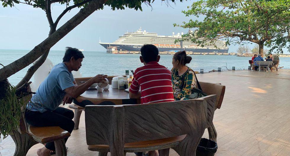 Fotografía de tres personas desayunando en un restaurante mientras observan el crucero Westerdam en Sihanoukville. (AFP).