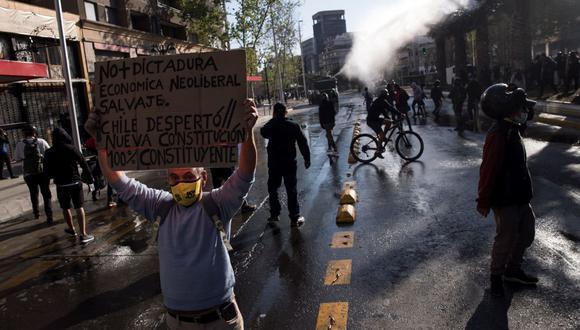 Un manifestantes sostiene un cartel durante una protesta en la Plaza Italia de Santiago. (EFE/Alberto Valdés).