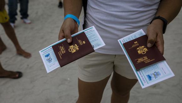 Una peruana sostiene pasaportes mientras espera en la fila para recibir la vacuna Johnson & Johnson contra el coronavirus Covid-19 en un centro de vacunación en la playa, en South Beach, Florida, el 9 de mayo de 2021. (Foto de Eva Marie UZCATEGUI / AFP).