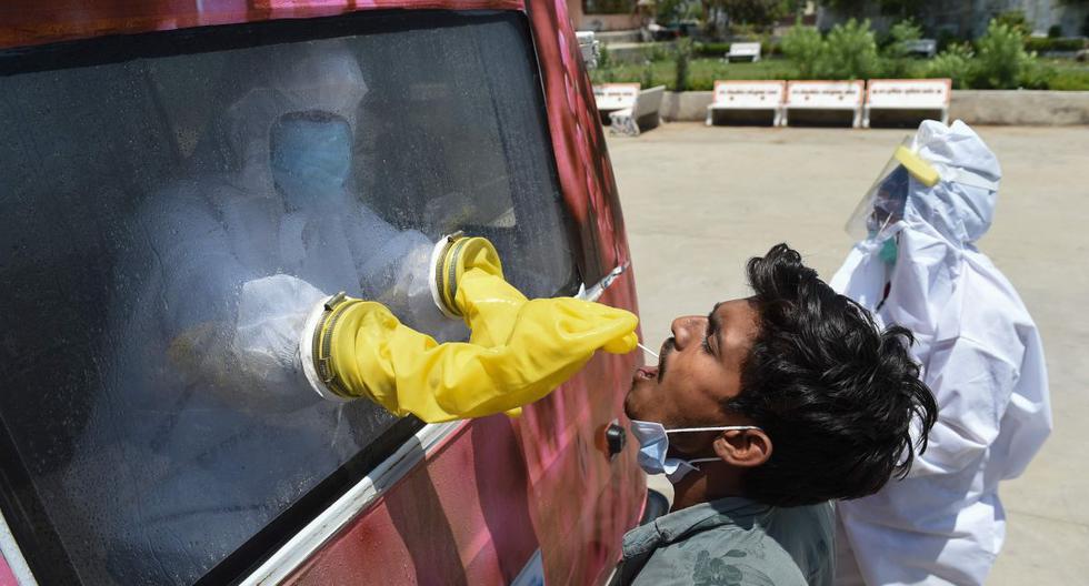Un funcionario de salud usa un hisopo para recolectar una muestra de un hombre en Changodar, pueblo a unos 20 kms de Ahmedabad (India), el 23 de abril de 2020. (AFP / SAM PANTHAKY).