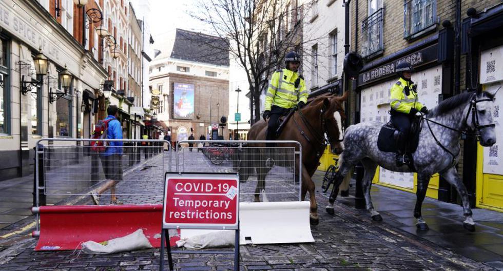 Los caballos de la policía pasan un cartel de COVID-19 en el centro de Londres, Reino Unido, el 15 de octubre de 2020.  (EFE/EPA/WILL OLIVER).