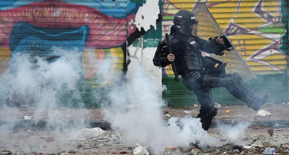 Un policía antidisturbios lanza un bote de gas lacrimógeno a los manifestantes durante una protesta contra una reforma fiscal propuesta por el gobierno en Cali, Colombia. (Foto de Luis ROBAYO / AFP).