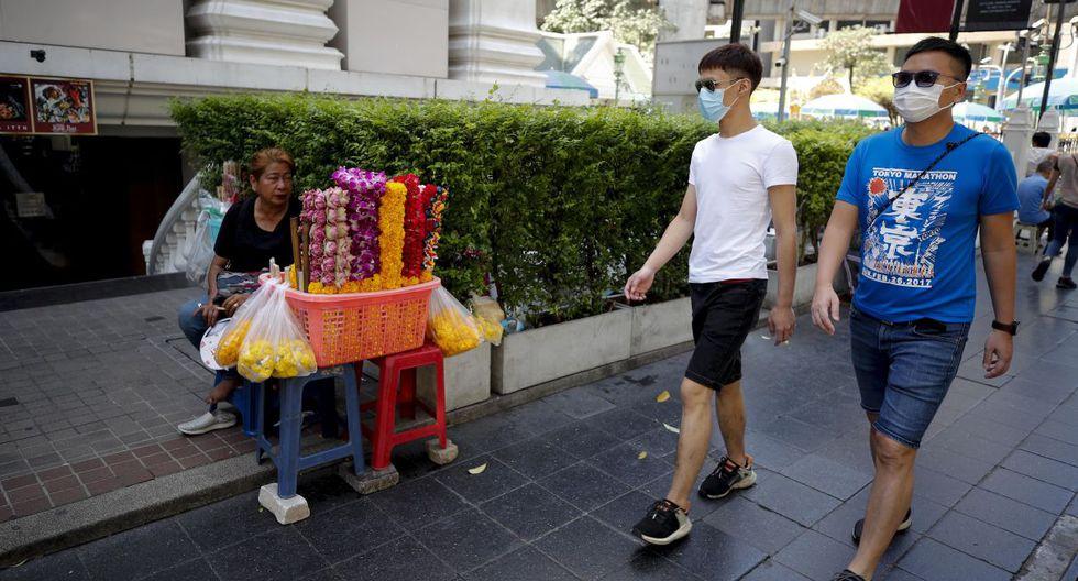 Los turistas chinos con máscaras de protección caminan frente a un vendedor ambulante en las inmediaciones del Santuario de Erawan en Bangkok. (EFE).