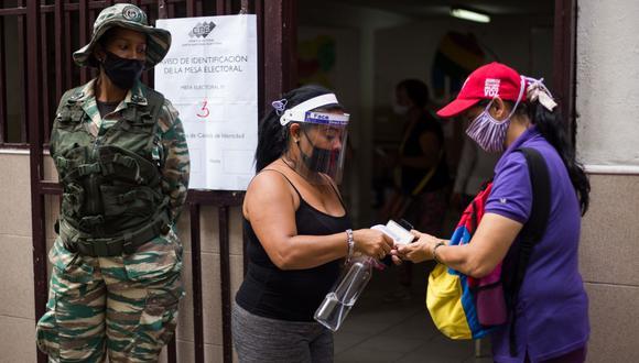 Un funcionario electoral rocía alcohol en las manos de una mujer mientras participan en una elección simulada para la próxima votación parlamentaria en Venezuela. (Cristian Hernandez / AFP)