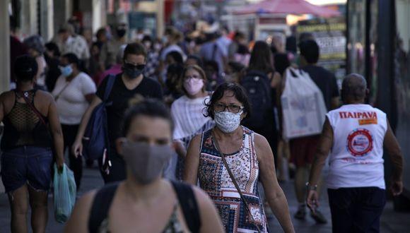 América se mantiene como el continente más golpeado por la pandemia. En la imagen un grupo de personas caminan por las calles de Brasil, país fuertemente golpeado por el coronavirus con 1,8 millones de infecciones.  (Foto: MAURO PIMENTEL / AFP)