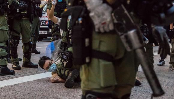La policía detiene a un hombre mientras patrulla las calles de Hong Kong, después de que los manifestantes convocaron una manifestación para protestar contra la decisión del gobierno de posponer las elecciones del consejo legislativo debido alCOVID-19 y la ley de seguridad nacional.(DALE DE LA REY / AFP)