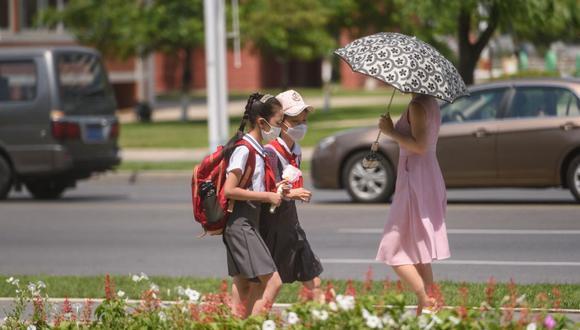 Las estudiantes caminan por una calle durante las altas temperaturas en Pyongyang (Corea del Norte), el 21 de julio de 2021. (Foto de KIM Won Jin / AFP).