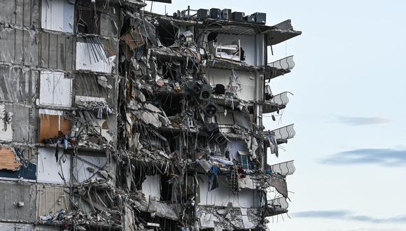 Escombros cuelgan del edificio parcialmente derrumbado en Surfside, al norte de Miami Beach. (Foto de CHANDAN KHANNA / AFP).