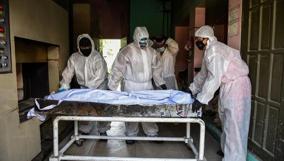 Personnel in protective suits, used due to the COVID-19 coronavirus outbreak, prepare to move a body inside the crematory chambers at a crematorium facility in Manila on April 29, 2020. - Most of the Philippines is under quarantine to contain the spread of the coronavirus that has infected over 7,000 people and killed at least 500 in the country. (Photo by Maria TAN / AFP)