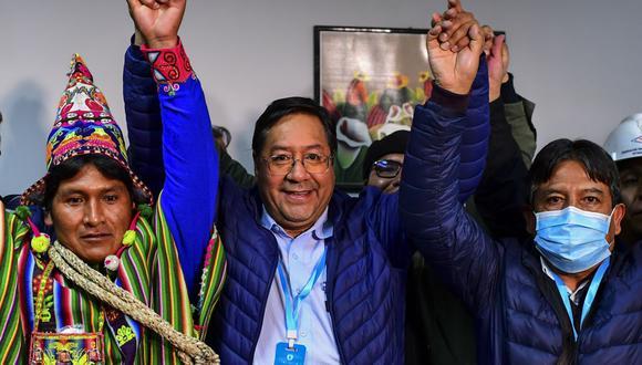 Luis Arce (centro), del partido Movimiento por el Socialismo, celebra con su compañero de fórmula David Choquehuanca (derecha) su triunfo en las elecciones en Bolivia. (Foto de RONALDO SCHEMIDT / AFP).