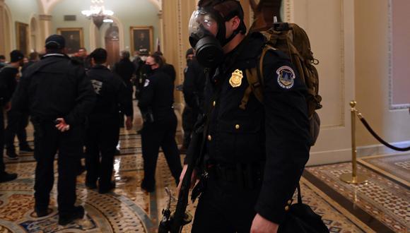 Un oficial de Policía del Capitolio viste una máscara de gas al enfrentar la violencia desatada por los partidarios de Donald Trump en el Congreso de Estados Unidos. (Foto: AFP)