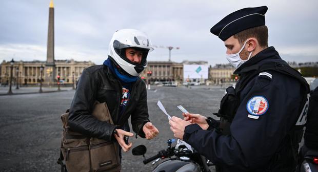 Los policías franceses controlan a un ciudadano en la Place de la Concorde, en París (Francia), el 13 de noviembre de 2020. (Anne-Christine POUJOULAT / AFP).
