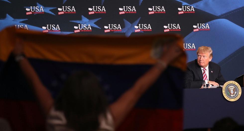 Se sostiene una bandera de Venezuela mientras el presidente de Estados Unidos, Donald Trump, asiste a una reunión en Florida. (Joe Raedle/Getty Images/AFP).