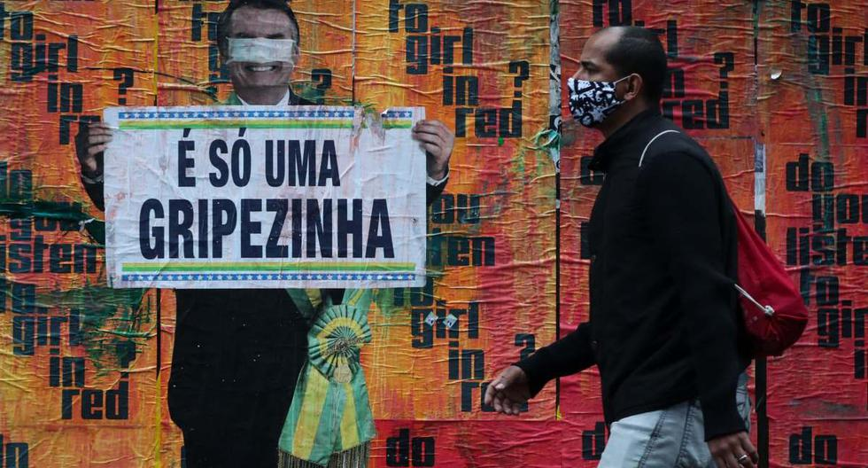 """Un ciudadano camina junto a una imagen del presidente brasileño Jair Bolsonaro sosteniendo un cartel con su polémico comentario sobre la COVID-19 al inicio de la pandemia, """"Es solo una gripecita"""", en un muro junto a la avenida Paulista, en Sao Paulo (Brasil). (EFE/ FERNANDO BIZERRA)."""