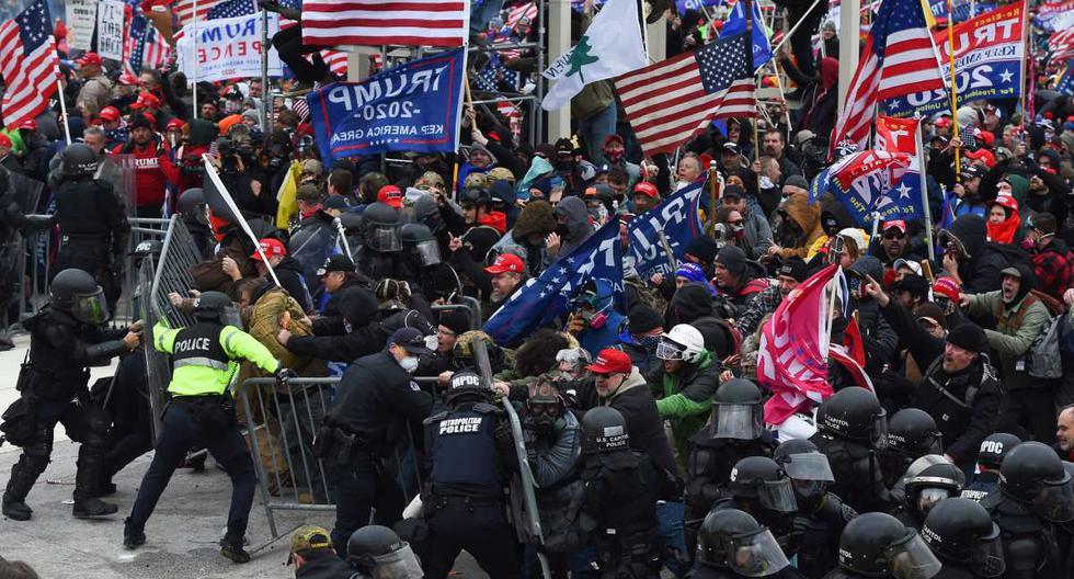 Los partidarios de Trump chocan con la policía y las fuerzas de seguridad mientras empujan barricadas para asaltar el Capitolio de los Estados Unidos, en Washington, el 6 de enero de 2021. (ROBERTO SCHMIDT / AFP).